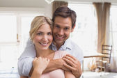Happy man embracing woman from behind at home — Stock Photo