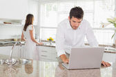 Man using laptop with woman in background at kitchen — Stockfoto