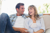 Loving young couple sitting on couch — Stock Photo