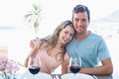 Loving couple with wine glasses at dining table — Stock Photo