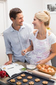 Happy young couple preparing cookies in kitchen — Stock Photo