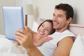 Couple using digital tablet in bed — Stock Photo