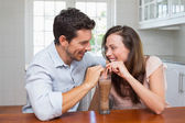 Loving young couple sharing a drink — Stock Photo