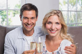 Cheerful young couple with champagne flutes at home — Stock Photo
