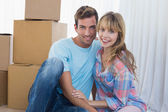 Couple sitting against cardboard boxes in new house — Stock Photo