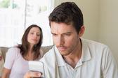 Woman looking at man text messaging — Stockfoto