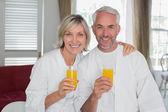 Happy mature couple holding orange juices — Stock Photo