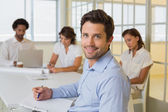 Smiling businessman with colleagues in meeting in at office — Stock Photo