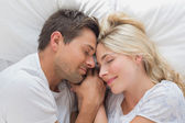 Loving couple lying in bed with eyes closed — Stock Photo