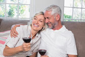 Loving mature couple with wine glasses in living room — Stock Photo