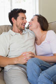 Cheerful relaxed couple sitting on couch — Stock Photo
