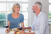 Mature couple with wine glasses having food — Stock Photo
