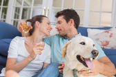 Couple with wine glasses and pet dog in living room — Stock Photo