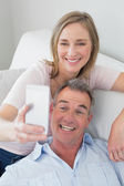 Couple clicking pictures with mobile phone at home — Stock Photo