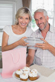 Mature man giving a gift box to happy woman — Stockfoto