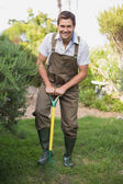 Happy man in dungarees raking the garden — Stock Photo