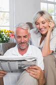 Mature couple reading newspaper — Stock Photo