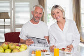 Couple reading newspaper while having breakfast — Stock Photo