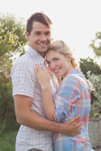 Smiling young couple embracing in the park — Stock Photo