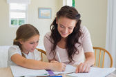 Woman helping daughter in homework — Stock Photo