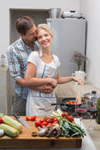 Young couple preparing food together in kitchen — Stock Photo