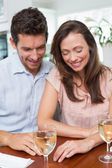 Couple with wine glasses at dining table — Stock Photo