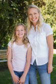 Mother with arm around daughter standing in park — Stock Photo