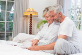 Relaxed mature couple reading book in bed — Stock Photo