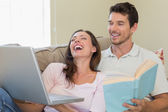 Cheerful couple with laptop and book sitting on couch — Stock Photo