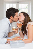 Loving young couple kissing with wine glasses — Stock Photo