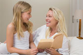 Mother and daughter with novel in bed — Photo