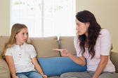 Mother scolding girl while sitting on sofa — Stock Photo