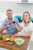 Couple toasting wine glasses in kitchen — Stock Photo