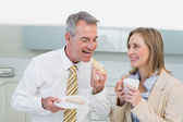 Happy business couple having breakfast in kitchen — Stock Photo