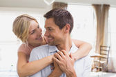 Woman embracing man from behind at home — Stockfoto