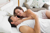 Happy relaxed couple together in bed — Stock Photo