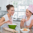 Girl helping her mother prepare food in kitchen — Stock Photo #42600177