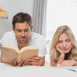 Relaxed couple reading books in bed — Stock Photo #42601363