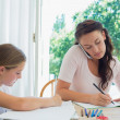 Woman using mobile phone while daughter studying at table — Stock Photo #42601901