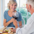 Mature couple toasting wine glasses over food — Stock Photo #42602021