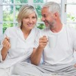 Smiling mature couple with coffee cups sitting on bed — Stock Photo #42603195