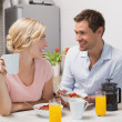 Couple looking at each other while having breakfast at home — Stock Photo