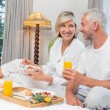 Mature couple having breakfast in bed — Stock Photo #42603449