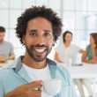 Smiling businessman having coffee with colleagues in background — Stock Photo #42603503