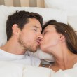 Relaxed couple kissing in bed — Stock Photo #42603649