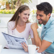 Smiling couple reading newspaper at cafe — Stock Photo