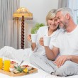 Smiling mature couple with coffee cups sitting on bed — Stock Photo #42604389