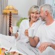 Mature couple having breakfast in bed — Stock Photo