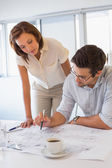 Concentrated colleagues working on blueprints at office — Stock Photo