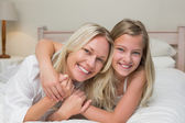 Loving mother and daughter lying in bed — Foto de Stock